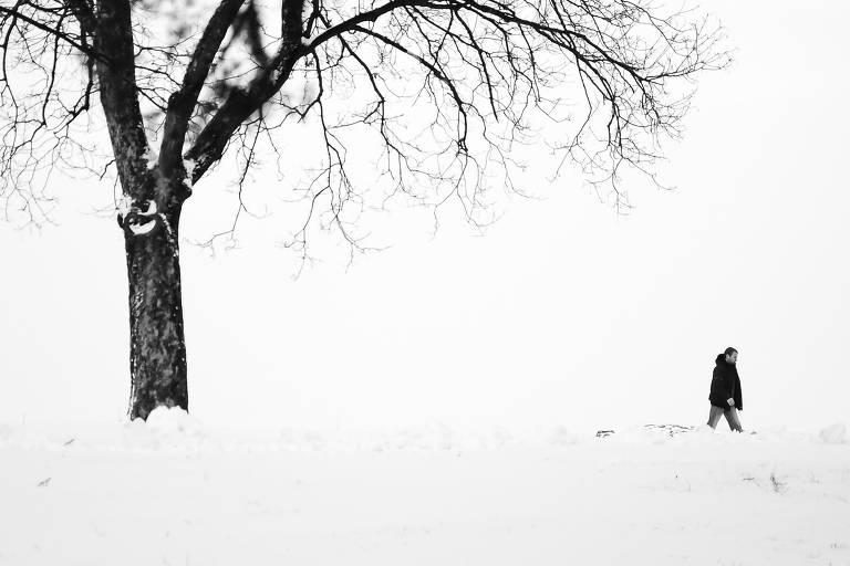 Foto em preto e branco mostra apenas um homem, a distância, caminhando, e uma árvore sem folhas à sua esquerda. Toda a paisagem é branca, pois o chão está coberto de neve e o dia está nublado