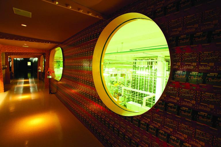 Duas janelas redondas e grandes em um corredor mostram as máquinas da fábrica da Nestlé. O corredor tem iluminação quente e espaçada, dando destaque à fábrica