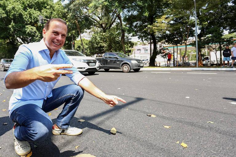 Homem agachado mostra o chão