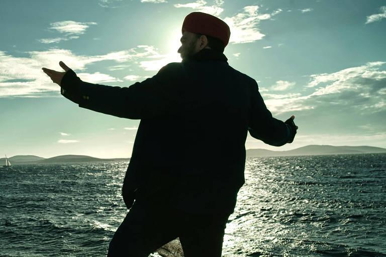Foto mostra o músico André Abujamra contra a luz, de costas, o rosto de perfil, com turbante, voltado para o mar