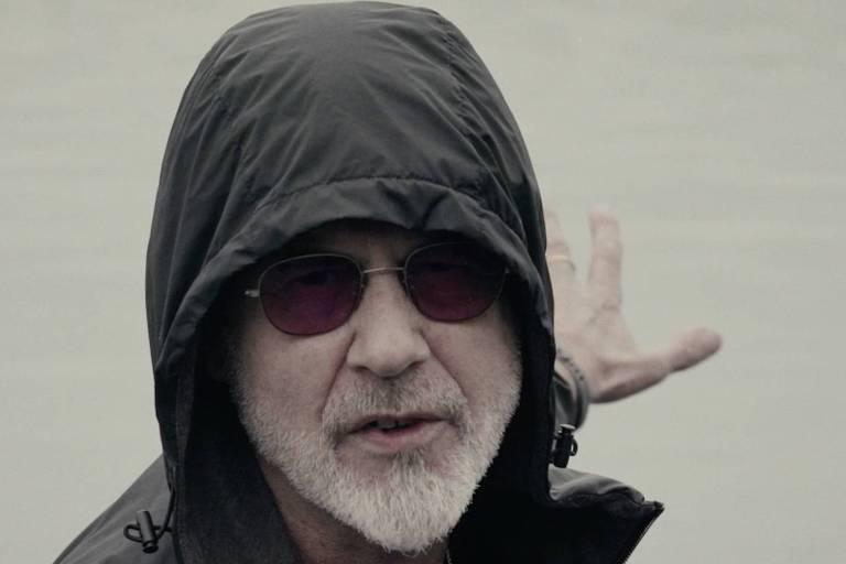 """O músico Ritchie, que gravou no Rio voz para """"Omindá - A União das Almas do Mundo pelas Águas"""", aparece de casaco de capuz preto e óculos escuros num cenário branco que parece uma praia"""