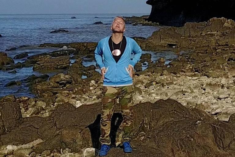 """O músico Martín Buscaglia, de pé de roupa esportiva numa praia; ele é um dos convidados de André Abujamra para o álbum/filme """"Omindá - A União das Almas do Mundo pelas Águas"""