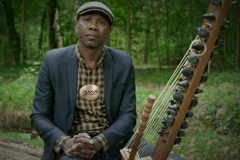 """O músico malinês Ballaké Sissoko, num cenário verdejante, ao lado de seu instrumento musical, uma kora, que é uma espécie de harpa-alaúde africana; ele é um dos convidados de André Abujamra para o álbum/filme """"Omindá - A União das Almas do Mundo pelas Águas"""""""