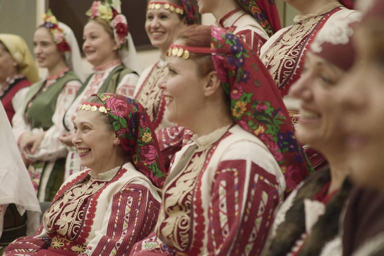 """Foto mostra cantoras com trajes típicos nas cores branco e vermelho, com lenços floridos na cabeça; elas são parte do grupo The Mystery of Bulgarian Voices; o grupo búlgaro, de Sofia, faz coro em """"Omindá - A União das Almas do Mundo pelas Águas"""""""