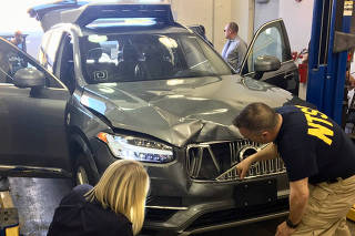 Handout photo of NTSB investigators examining a self-driving Uber vehicle involved in a fatal accident in Tempe