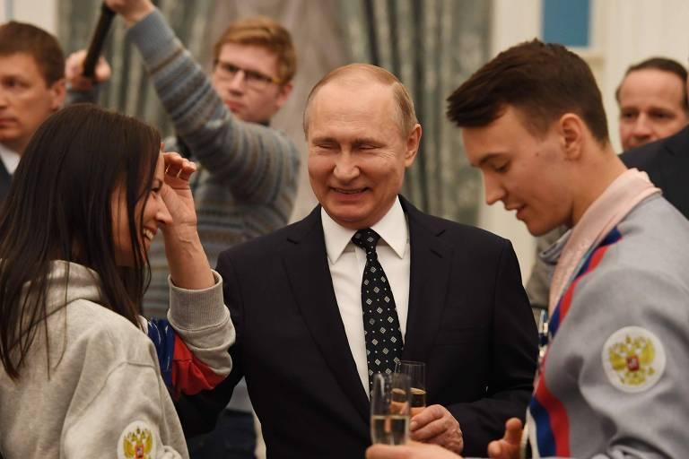 Com taça de espumante na mão, o presidente da Rússia, Vladimir Putin, ri entre dois atletas olímpicos: um homem de cabelo curto castanho à direita e uma mulher de cabelo comprido escuro à esquerda, durante celebração aos participantes dos Jogos Paralímpicos de Inverno de Pyeongchang, na Coreia do Sul