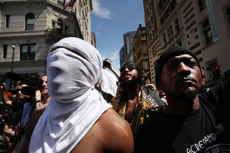 Em meio a manifestantes em uma rua de Boston, nos EUA, dois homens negros aparecem à frente: um de camiseta preta e outro sem camisa, mas cobrindo o rosto com uma camiseta branca; ao fundo, outro homem negro, com roupas de estilo afro