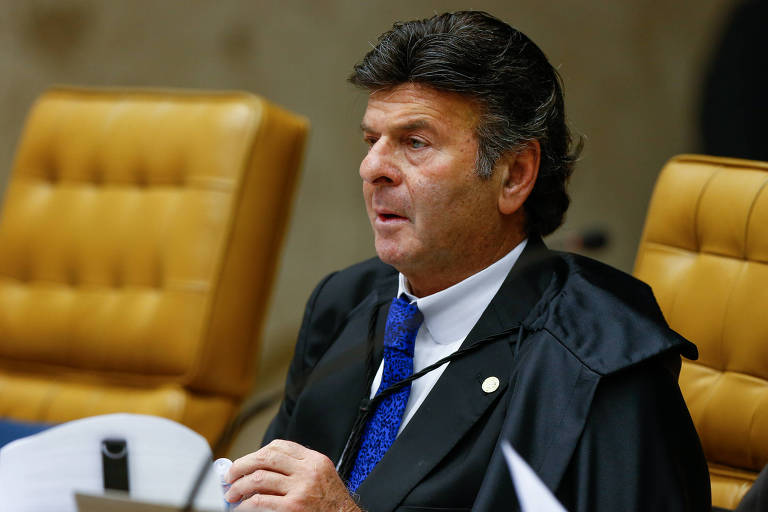 Luiz Fux, com capa preta, sentado em cadeira amarela do plenário do STF