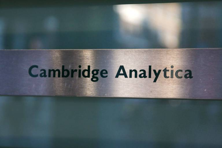 Nome Cambridge Analytica aparece em letras verdes em placa prateada de metal em vidro do prédio da empresa