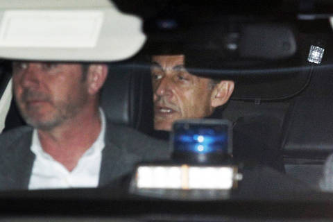 Former French President Nicolas Sarkozy, right, leaves the police station where he was held, in Nanterre, outside Paris, Wednesday March 21, 2018. Former French President Nicolas Sarkozy was questioned by police for a second day Wednesday over allegations he took millions of euros in illegal campaign funding from the late Libyan leader Moammar Gadhafi. (AP Photo/Francois Mori) ORG XMIT: XCE202