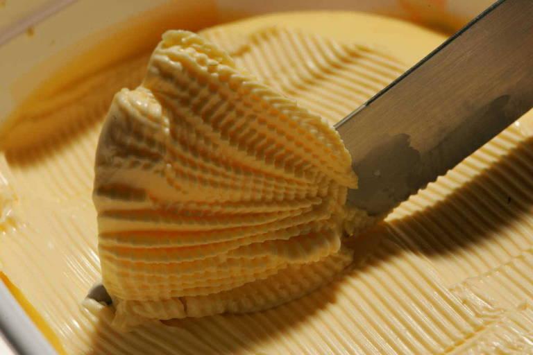 Faca sendo passada sobre e acumulando margarina