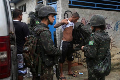 An armed forces members inspect a man during an operation against drug dealers in Vila Kennedy slum in Rio de Janeiro, Brazil March 8, 2018. REUTERS/Pilar Olivares ORG XMIT: PON02