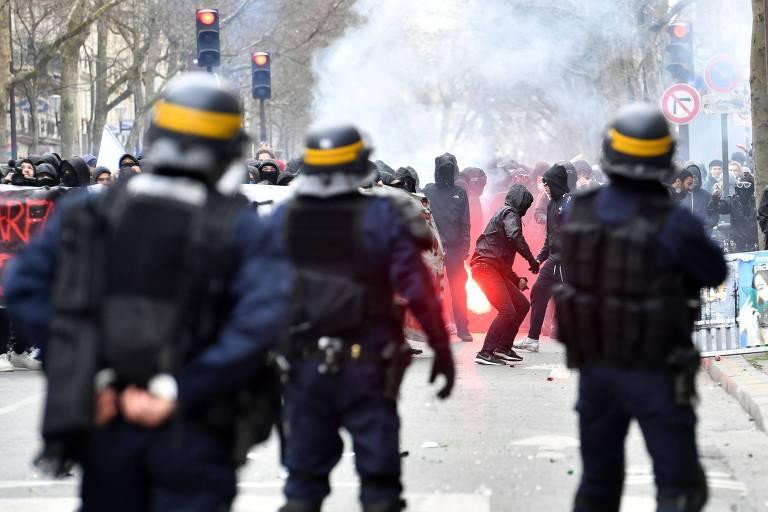 Policiais observam manifestantes em Paris durante protesto contra as reformas de Macron