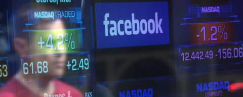 (FILES) In this file photo taken on May 17, 2012, a Facebook logo is seen through the windows of the NASDAQ stock exchange as people walk by on Times Square in New York. Facebook shares tumbled 5.0 percent in early trading on March 19, 2018, following reports of a large data breach as US stocks fell ahead of a US Federal Reserve policy decision later this week. Of the major indices, Facebook weighed most heavily on the tech-rich Nasdaq Composite Index, which was down 0.9 percent to 7,411.34 about 20 minutes into trading.  / AFP PHOTO / Emmanuel DUNAND ORG XMIT: ED098