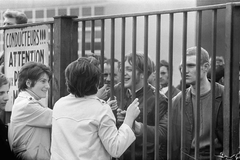 Foto em preto e branco mostra duas mulheres jovens conversando com rapazes do outro lado de uma grade
