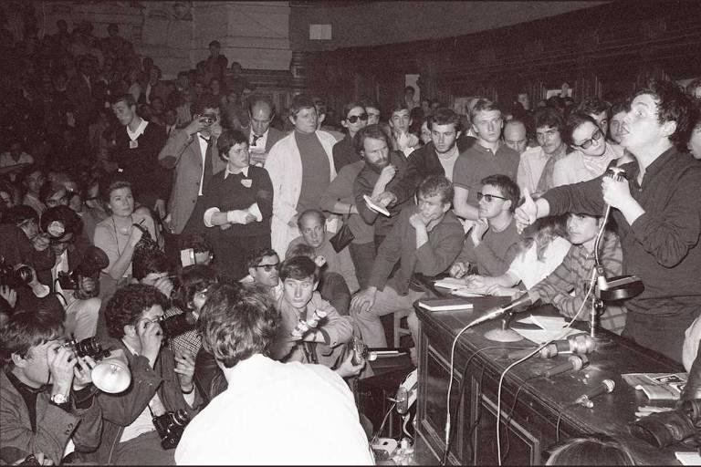 Foto em PB mostra estudante discursando a uma sala cheia , diante de uma mesa; há mais de 50 pessoas na imagem