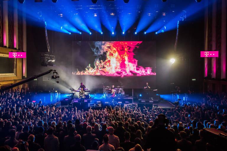 Foto mostra público e o palco, distante, durante show do Depeche Mode