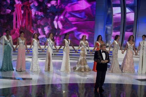 FILE - In this Oct. 9, 2014 file photo, Miss Venezuela President Osmel Sousa poses in front of the ten semi-finalist during the Miss Venezuela 2014 beauty pageant in Caracas, Venezuela. The Miss Venezuela Organization said in a statement on Wednesday, March 21, 2018 it will temporarily suspend its activities to do an internal review of its ethics policy. The review follows social media posts alleging some former participants benefited economically from their relationships with government figures. (AP Photo/Fernando Llano, File) ORG XMIT: XLAT150