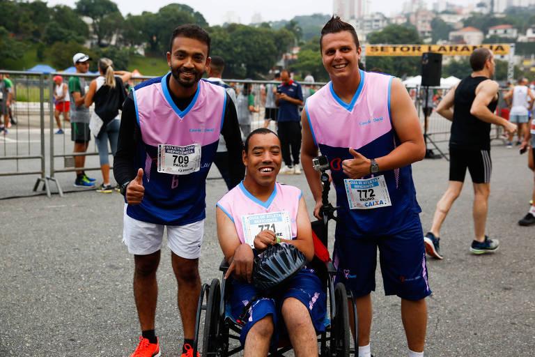 Alexandre Barros de Lima, 38, cadeirante com paralisia cerebral, acompanhado pelo professor de educação física Bruno Sartori (dir) e o fisioterapeuta Paulo Souza na Meia Maratona de SP