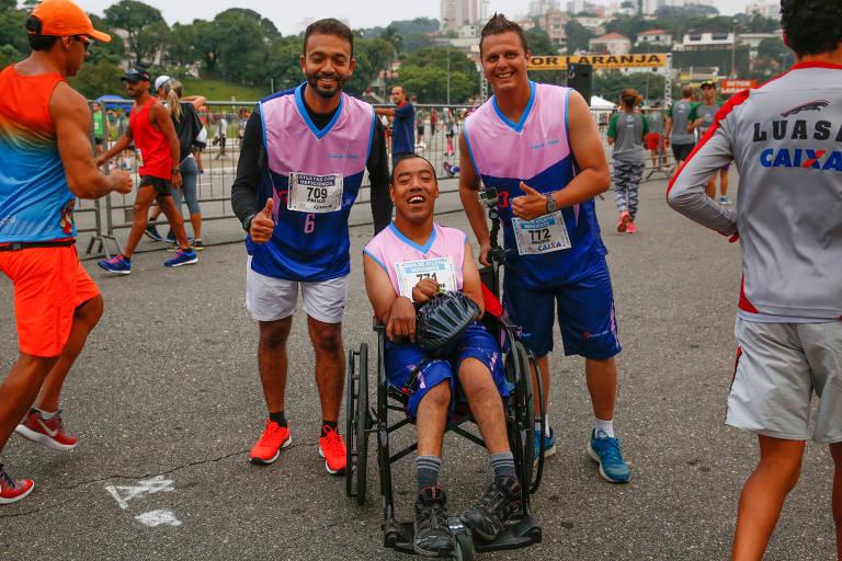 Alexandre Barros de Lima, 38, com sua cadeira improvisada, acompanhado pelo professor de educação física Bruno Sartori (dir) e o fisioterapeuta Paulo Souza na Meia Maratona de SP