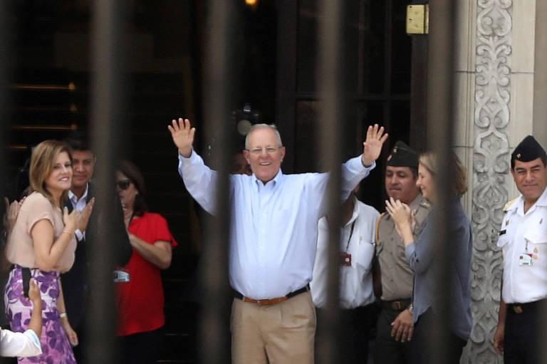 O ex-presidente do Peru Pedro Pablo Kuczynski sorri e levanta os dois braços para acenar a seguidores ao deixar o Palácio do Governo, em Lima; ele aparece por trás das grades do palácio