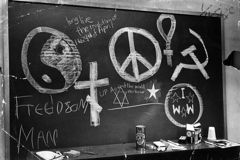 Símbolos de Yin-Yang, da cruz, da foice e do martelo do comunismo, de paz de amor e a estrela de Davi aparecem entre os desenhos em um quadro-negro de uma sala ocupada por manifestantes em Columbia