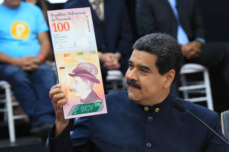O ditador venezuelano, Nicolás Maduro, exibe modelo de nota de 100 bolívares durante evento em Caracas