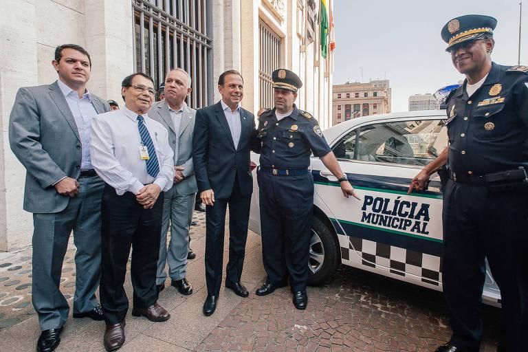 Abraçado com o prefeito João Doria, o atual comandante geral da GCM, Carlos Alexandre Braga (apontando para o carro); de terno claro ao lado de Doria, o secretário da Segurança Urbana, José Roberto Rodrigues de Toledo