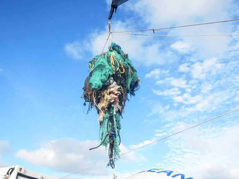 Rede de pesca abandonada sendo içada do oceano