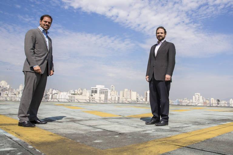 Da esq. para a dir., os secretários municipais Paulo Uebel (Gestão) e Caio Megale (Fazenda), em visita à Folha. Ambos posaram para a foto no topo do prédio do jornal, com o céu azul ao fundo
