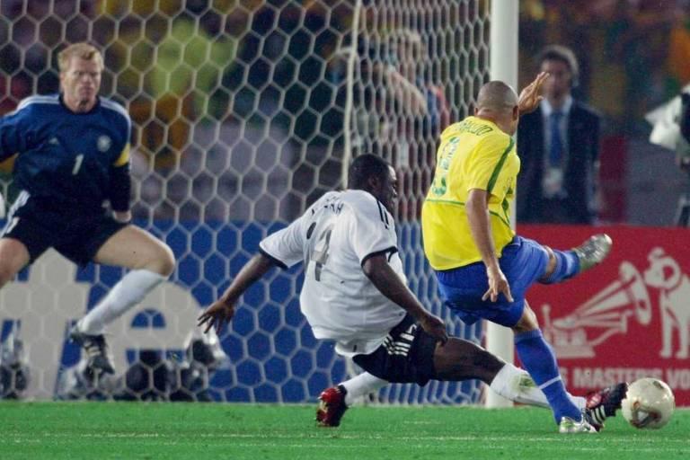 O atacante Ronaldo (à dir.) se antecipa ao zagueiro Asamoah e bate de direita, à esquerda do goleiro Oliver Kahn na vitória diante Alemanha, assegurando o pentacampeonato para o Brasil na final da Copa do Mundo da Coréia e do Japão