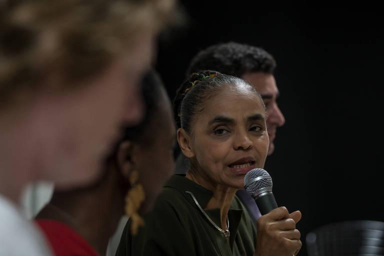 A ex-senadora Marina Silva fala ao microfone durante evento e olha para outros participantes da mesa
