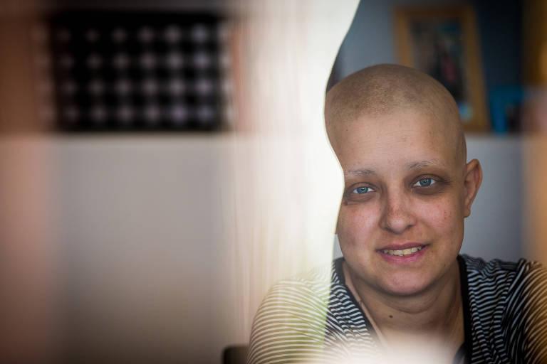Angel Almeida, 28, careca por conta do tratamento contra o câncer, sorri para a foto