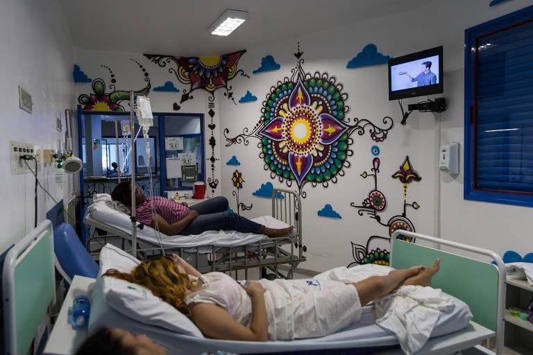 Grafite de uma mandala na parede de ala destinada a jovens adultos. No quarto, há cama ocupadas por pacientes