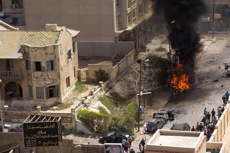 Área da explosão em Alexandria, com prédios danificados e uma coluna de fogo subindo da rua, por onde passou o chefe de segurança da cidade