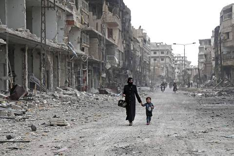 TOPSHOT - A Syrian woman and child walk down a destroyed street as civilians and rebels prepare to evacuate one of the few remaining rebel-held pockets in Arbin, in Eastern Ghouta, on the outskirts of the Syrian capital Damascus, on March 24, 2018.