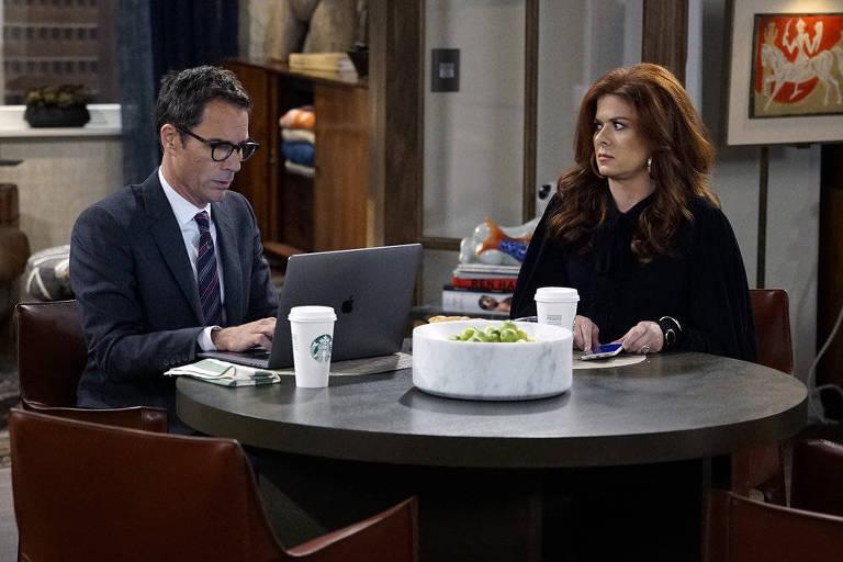 """Foto de episódio da volta de """"Will & Grace"""" mostra Eric McCormack (Will) de óculos, trabalhando sério ao laptop, de óculos, enquanto Debra Messing (Grace), sentada à mesma mesa redonda, o observa com cara de espanto, segurando um celular"""