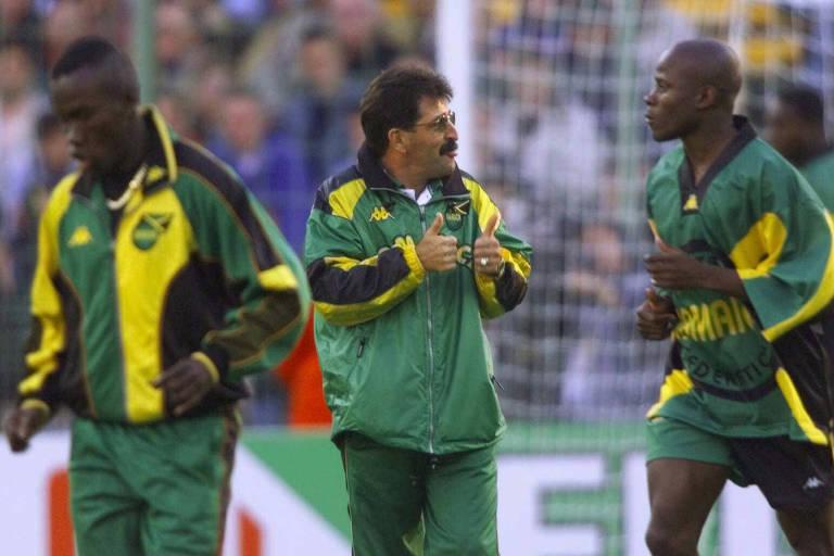 Homem com óculos e roupa verde conversa com outro homem também de verde, em campo de futebol