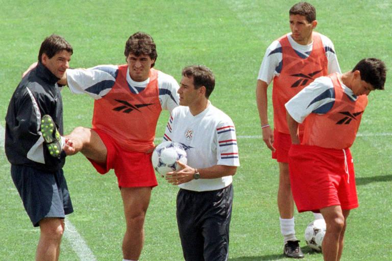 Cinco homens em campo de futebol, o do centro segura uma bola na mão, enquanto os outros fazem alongamento