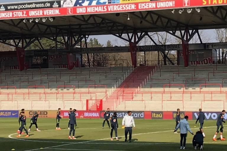 Homens em campo, dentro de estádio de futebol vazio