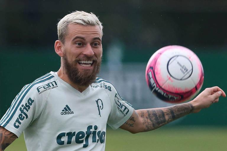 Homem com camisa branca sorri, há uma bola na altura do seu ombro