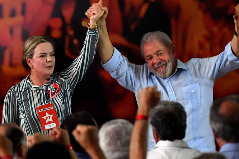 Gleisi Hoffmann segurando e erguendo a mão de Lula
