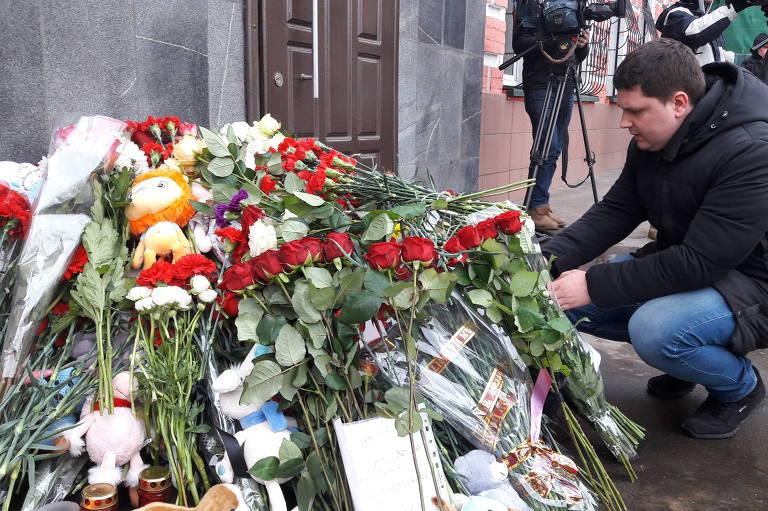 homem coloca flores em memorial a vítimas de incêndio