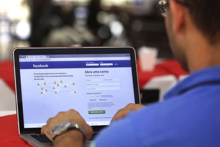 Homem em frente ao computador abre página do Facebook