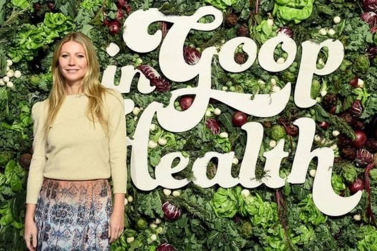 Atriz Gwyneth Paltrow posa para foto ao lado do logo de seu site sobre saúde