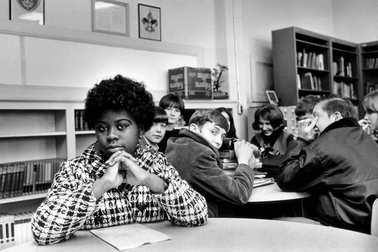Linda Brown aparece sentada à mesa de uma biblioteca ao lado de outra mesa com crianças brancas; ao fundo, estantes baixas de livros