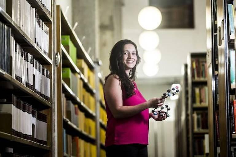 A cientista Rafaela Salgado Ferreira em meio a estantes de livros