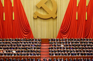 FILE PHOTO: Chinese President Xi Jinping and fellow delegates raise their hands as they take a vote at the closing session of the 19th National Congress of the Communist Party of China, in Beijing