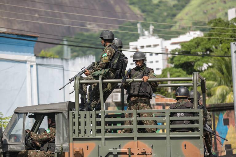Militares ocupam carroceria de caminhão do Exército e seguram armas durante patrulhamento