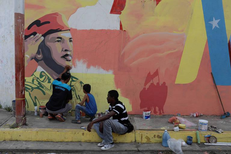 Homem pinta mural com imagem do ex-presidente Hugo Chávez antes de celebração em Elorza, na Venezuela